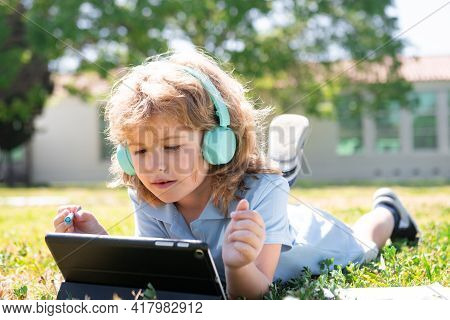 Little Schoolboy Pupil Use Notebook Or Tablet In The Park On Grass. Self Education, Kid Learning And