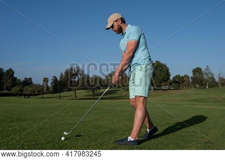 Golf Player Playing Golf On Sunny Day. Professional Golfer Taking Shot On Golf Course.