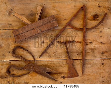 Aged rusted traditional tools wood planer wool scissors drawing compass on retro wood
