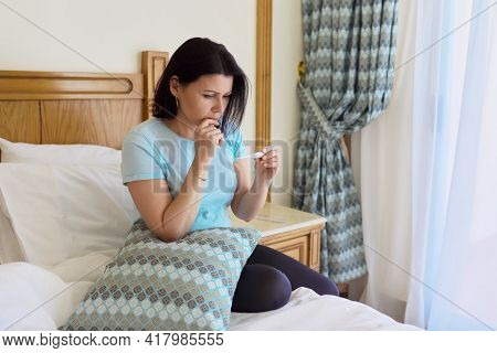 Sad Sick Mature Woman Holding Thermometer In Her Hands, Sitting At Home In Bed