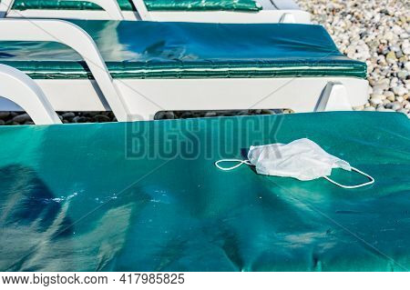 A Disposable Face Mask On Chaise Longue At Beach