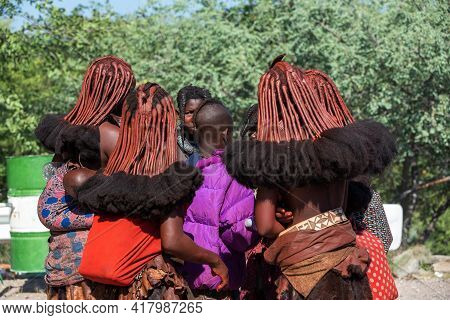 Namibia, Omusati Region, May 7: Group Of Young Himba Woman With Traditional Hairstyle And Red Clay P