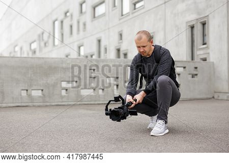 Filmmaking, Hobby And Creativity Concept - Professional Male Videographer Shooting Video Using Moder