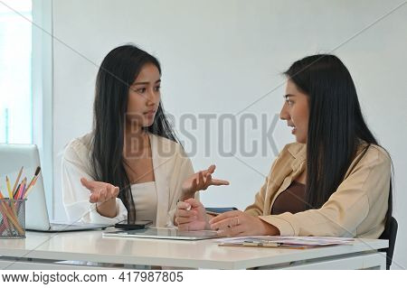 Two Female Students Have Serious Conversation While Doing Their Group Assignment