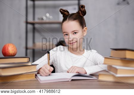 School, Homework And Education Concept - Portrait Of Happy Cute School Girl Writing Something In Tex