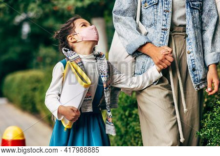 Horizontal Image Of A Happy Kid Wearing Protective Face Mask Going Back To The School With Her Mothe