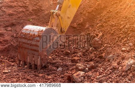 Backhoe Working By Digging Soil At Construction Site. Bucket Of Backhoe Digging Soil. Crawler Excava