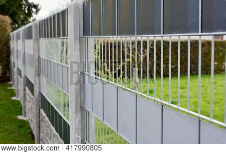 Garden Fence Made With Decorative Galvanized Wire Fence Panels Inserted In To The Concrete Columns.