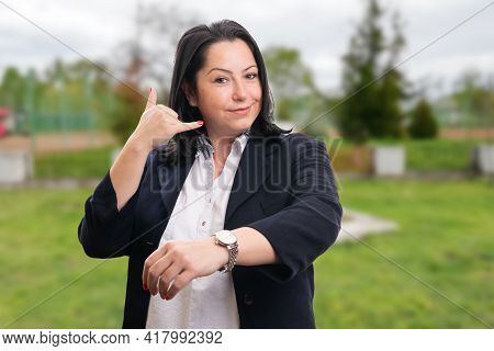 Corporate Woman Entrepreneur Wearing Suit Smiling Making Calling Gesture With Fingers Showing Watch