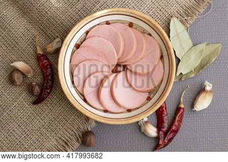 Appetizing Sausage Sliced On A Grey Plate On A Rough Linen Background With Chilli Pepers And Spices,