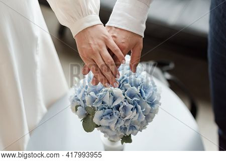 Wedding Couple Holding Hands Above Wedding Bouquet. Love And Marriage Concept