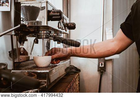 View Of Barista Hand Using Espresso Machine To Making Espresso Coffee Shot. The Espresso Machine Is