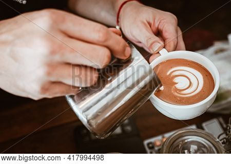 Barista Pouring Steamed Milk To Hot Coffee To Making Latte Art. A Latte Is A Coffee Drink Made With