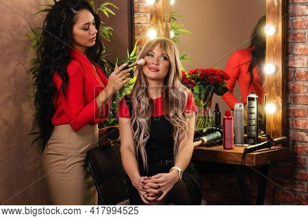 Professional Makeup Artist Doing Makeup For Beautiful Blonde Woman On Beauty Salon Background. Real