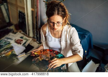 Top View Of A Pretty Girl Artist Painting With A Brush On Canvas In Her Art Studio. A Woman Painter