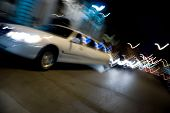 An abstract blur of a white limousine in the city at night with light trails. poster