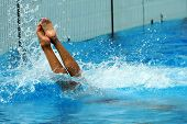 Woman jumping getting into water in diving action poster