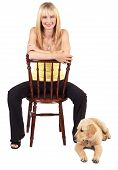 Portrait of a beautiful blonde woman with light blue eyes and colorful make-up sitting on a chair with golden retriever puppy next to her poster