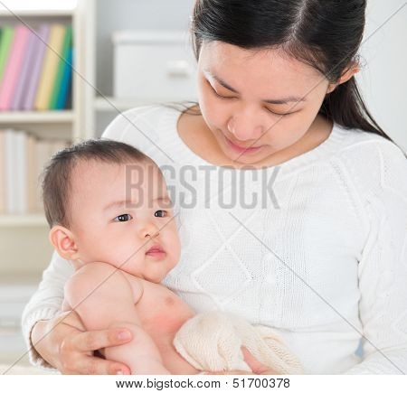 Beautiful Asian mother pampering six months old baby girl at home.