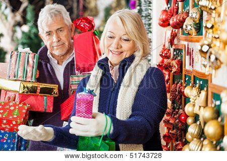 Happy senior woman shopping with man holding presents in Christmas store