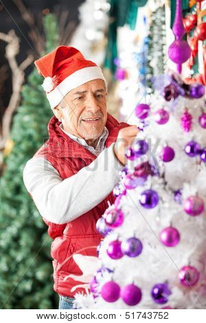 Senior male owner in Santa hat decorating Christmas tree with balls at store