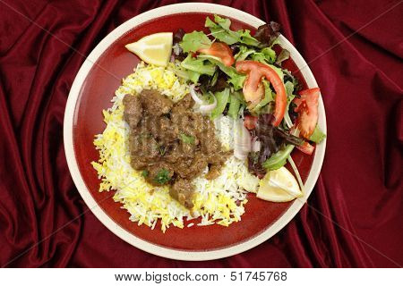 High-angle view of beef rogan josh, served with yellow and white rice and a salad. Rogan josh is usually made with lamb, as it is a Hindu dish, but works equally well with beef.