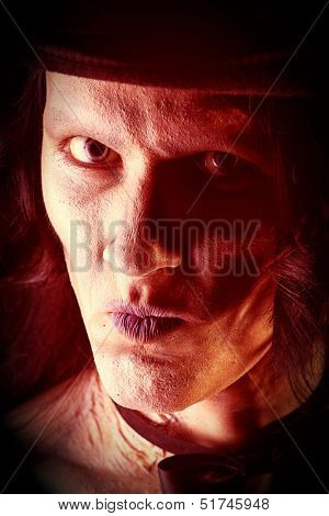 Close-up portrait of a gloomy vampire standing at the night background. Halloween.
