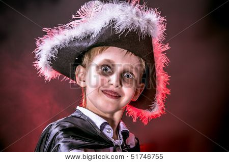 Little boy in halloween costume of pirate posing over dark background.