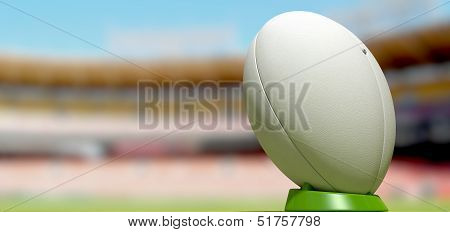 A plain white textured rugby ball on a green kicking tee in a stadium poster