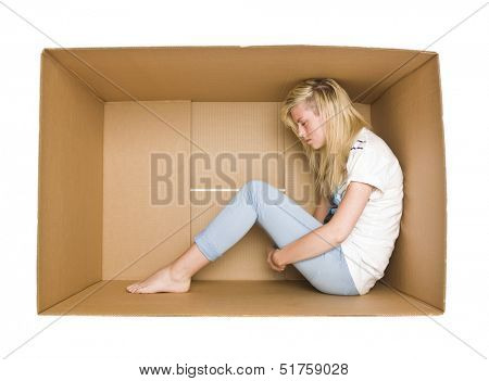 Woman siting in a cardboard box isolated on white background