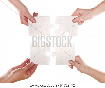 Four human hands with puzzle pieces connecting