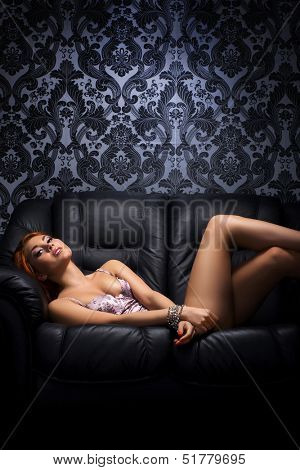 Young, sexy and beautiful girl in lingerie and the glamour handcuffs on the leather sofa