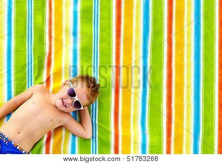 happy kid sunbathing on colorful blanket blanket poster