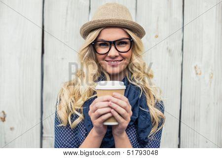 Fröhlich modische Blondine hält Kaffee im Freien auf hölzernen Hintergrund