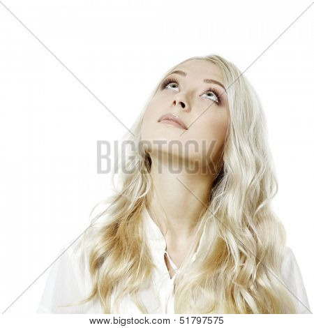 Young attractive blond girl looking up at copy space over white