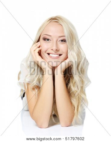 Beautiful blond teen girl lying, looking at camera and happy smiling. Isolated on white background