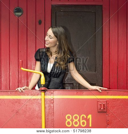 Beautiful young woman standing on a red train caboose car