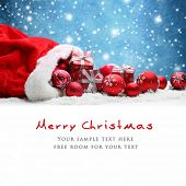Santa Claus red bag with Christmas balls and gift box on snow. poster