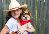 Beautiful cowboy kid girl holding chihuahua dog with sheriff hat in backyard wooden fence poster