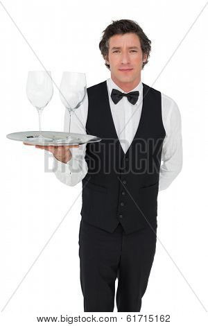Portrait of confident server carrying wine glasses isolated over white background