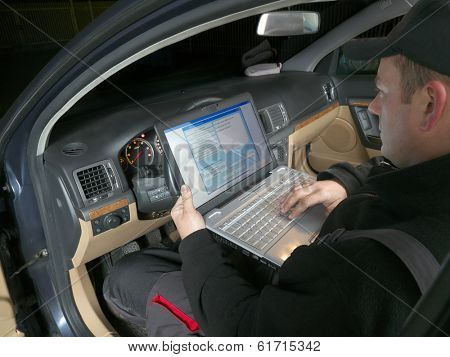 Auto mechanic checking vehicle identification number of the car using laptop hooked up to the car onboard computer poster