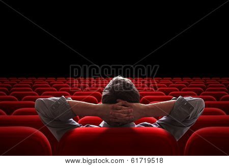 one man sitting in empty cinema or theater auditorium