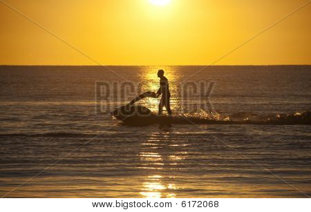 Trearddur Bay sunset with the a jet skier playing in the last rays of the sun poster