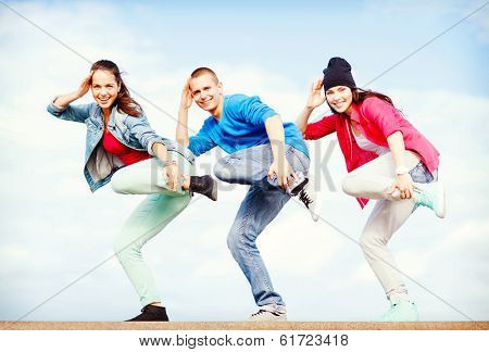 sport, dancing and urban culture concept - group of teenagers dancing poster