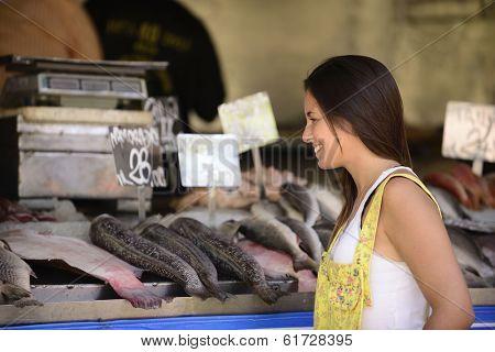 Happy beautiful woman buying fish at a fish shop street market.