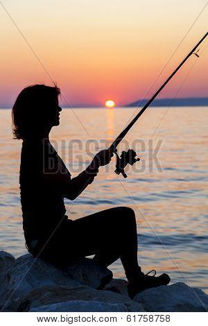 Woman silhouette fishing on rock