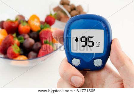 Hand Holding Meter. Diabetes Doing Glucose Level Test. Fruits In Background