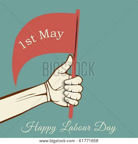 Human hand holding a flag with text 1st May on green background, concept for Happy Labour Day.