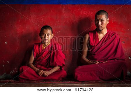 DISKIT, INDIA - SEPTEMBER 12, 2012: Unidentified adult and child Tibetan Buddhist monks in Diskit gompa (monastery) during prayer, Nubra valley, Ladakh, India
