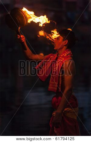 UJJAIN, INDIA - APRIL 24:, 2011 Brahmin performing Aarti pooja ceremony on bank of holy river Kshipra. Aarti is Hindu religious ritual of worship, part of puja when light is offered to deities